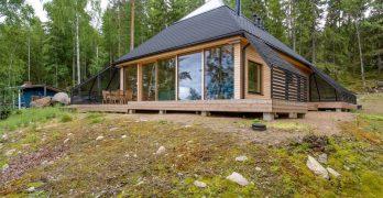 Casa prefabricada con techo piramidal y con paredes acristaladas con vistas al lago